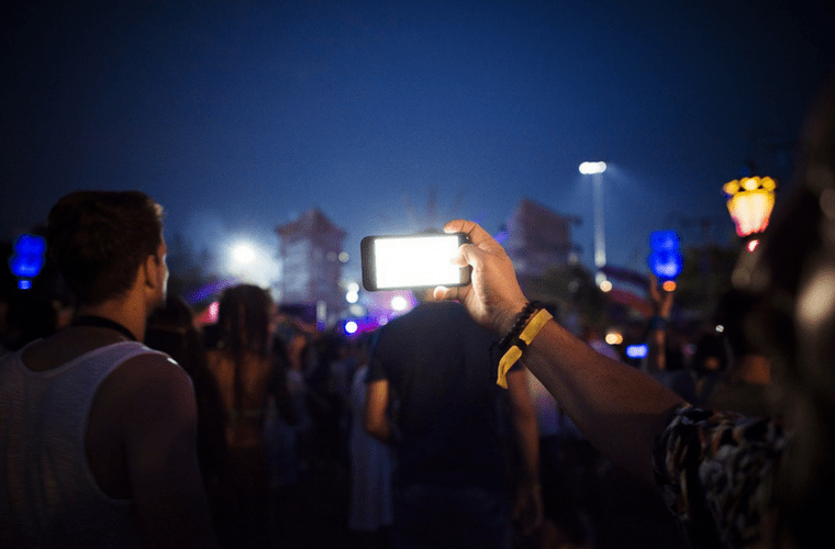a hand holding a smart phone taking a photo of a music concert