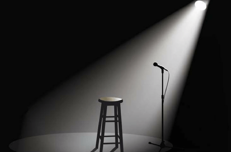 black and white photo of an empty stage with a stool and a microphone drenched in a spotlight